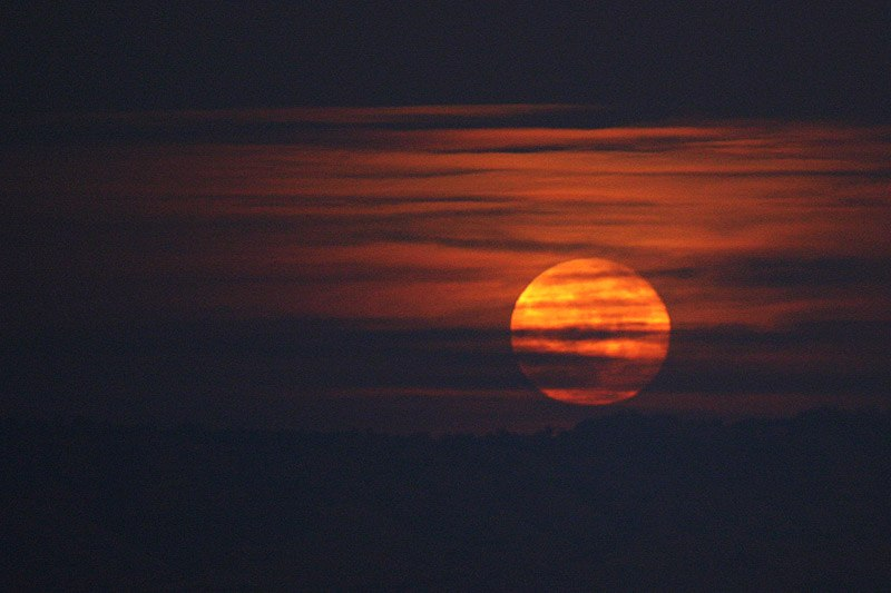 Harvest Moon Rising Behind Clouds